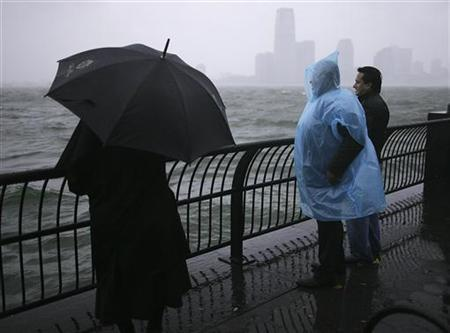 People look at waves at the New York Harbor as Hurricane Sandy approaches New York October 29, 2012. Hurricane Sandy, one of the biggest storms ever to hit the United States, lashed the densely populated East Coast on Monday, shutting down transportation, forcing evacuations in flood-prone areas and interrupting the presidential campaign. REUTERS/Carlo Allegri