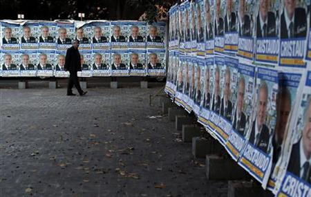 A man walks past posters of the Sicily regional candidate during regional elections in Catania October 28, 2012. REUTERS/Alessandro Bianchi