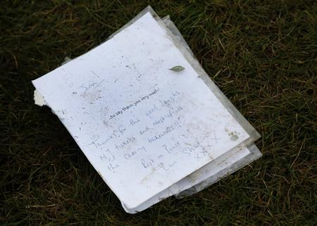 A card lays on the spot where the headstone was removed from the grave of British television star Jimmy Savile at a cemetery in Scarborough, northern England October 10, 2012. REUTERS/Phil Noble