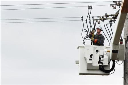 A power company worker in a cherry picker connects wires to a power line while working to restore electricity in East Massapequa, New York October 31, 2012. REUTERS/Lucas Jackson