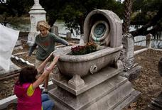 Olivia Cox, 9, (L) of Summerville, South Carolina and her friend Winslow Hastie, 8, of Charleston, check out a grave marker in the White Plot during the Tour de Graves at the Magnolia Cemetery in Charleston, South Carolina October 26, 2012. REUTERS/Randall Hill