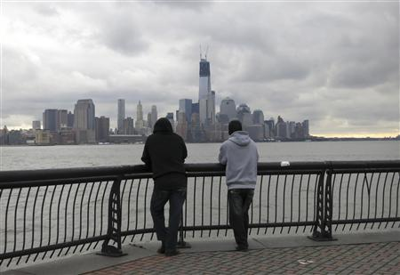 Two men look at the skyline of New York's Lower Manhattan from a park along the Hudson River in Hoboken, New Jersey, October 31, 2012. REUTERS/Gary Hershorn