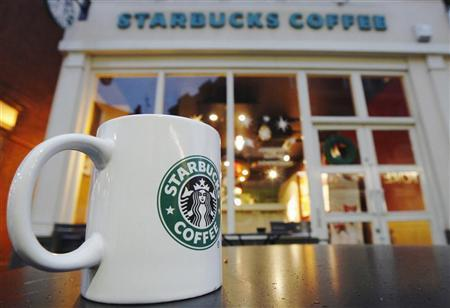 An empty cup is left on a table outside a Starbucks coffee shop in London December 1, 2011. Picture taken December 1, 2011. REUTERS/Luke MacGregor/Files