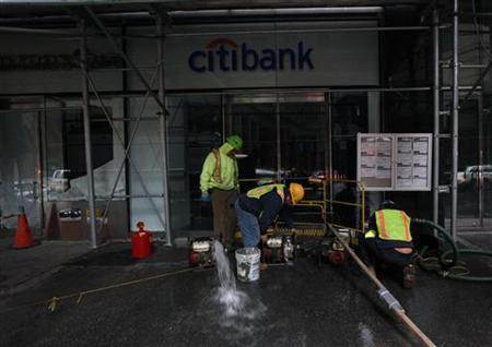 Workers pump water out of a flooded Citibank branch in New York's financial district October 31, 2012. REUTERS/Brendan McDermid