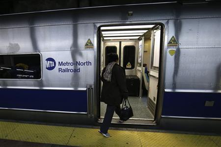 A woman boards the first Metro North commuter train to leave Grand Central Station in New York since 7pm EDT on Sunday October 28 departed as some train service was resumed following Hurricane Sandy, October 31, 2012. REUTERS/Mike Segar