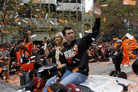 San Francisco Giants catcher Buster Posey, with his wife Kristen, waves as he rides through confetti at the Giants' World Series winners parade along Market Street in San Francisco, California October 31, 2012. REUTERS/Robert Galbraith