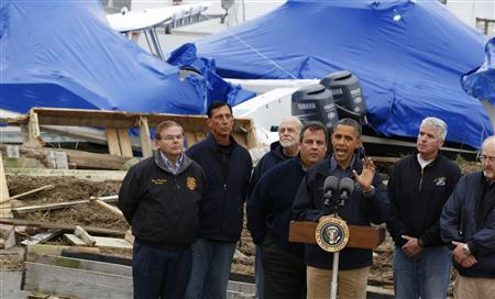 U.S. President Barack Obama (3rd R) speaks in a neighborhood after he tours damage done by Hurricane Sandy in Brigantine, New Jersey, October 31, 2012. REUTERS/Larry Downing