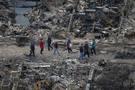 Residents walk past burned houses in Breezy Point, a neighborhood located in the New York City borough of Queens, after it was devastated by Hurricane Sandy October 31, 2012. REUTERS/Adrees Latif