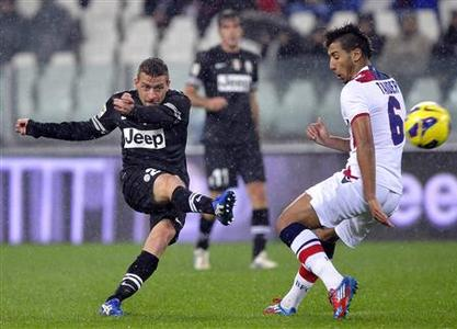 Juventus' Emanuele Giaccherini (L) shoots as Saphir Sliti Taider of Bologna challenges during their Serie A match at the Juventus stadium in Turin October 31, 2012. REUTERS/Giorgio Perottino