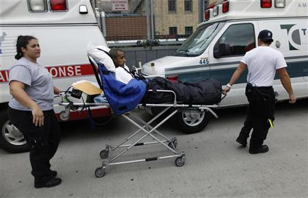 Paramedics wheel a patient out of Bellevue Hospital during an evacuation in the aftermath of Hurricane Sandy in New York October 31, 2012. REUTERS/Carlo Allegri