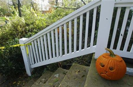 A 'sad faced' jack-o-lantern awaits trick or treaters on Halloween at a house with tree damage (rear) in Silver Spring, Maryland October 31, 2012. REUTERS/Gary Cameron