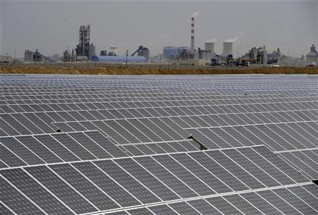 A solar power plant is seen near a thermal power plant in Aksu, Xinjiang Uyghur Autonomous Region May 18, 2012. REUTERS/Stringer