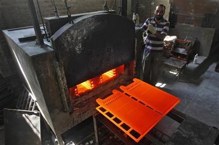 A worker stands next to a room heater manufacturing unit inside a factory in Srinagar October 1, 2012. REUTERS/Danish Ismail