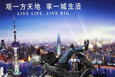 A man rests on a motorcycle in front of an advertisement in central Shanghai in this October 18, 2012 file photo. China's economy is finally regaining traction, official and private sector factory surveys showed on November 1, 2012, although the recovery remains sluggish with the latter recording its 12th straight month of slowing growth. REUTER/Aly Song/Files