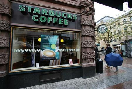 Pedestrians stand next a branch of Starbucks in Frankfurt October 30, 2012. REUTERS/Ralph Orlowski