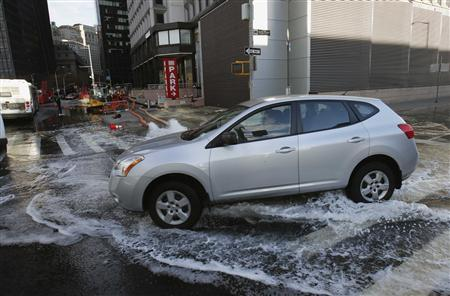 A car drives through water due to flooding from Hurricane Sandy in New York October 31, 2012. REUTERS/Mike Segar