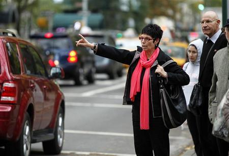 A woman tries to hail a taxi on the Upper East Side of Manhattan in the aftermath of Hurricane Sandy in New York October 31, 2012. REUTERS/Carlo Allegri