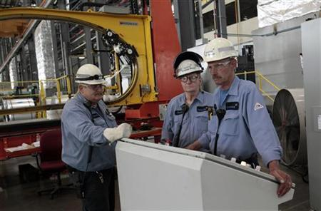 Severstal North America steel workers stand by the operating station for shrink wrapping steel