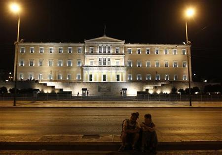 A couple sits in front of the parliament in central Athens October 6, 2012. REUTERS/John Kolesidis