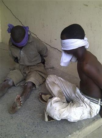 Men suspected to be members of Islamic sect Boko Haram sit blindfolded at a barrack after a shootout between the sect and the military in Nigeria's northern city of Kano March 20, 2012. REUTERS/Bala Adamu