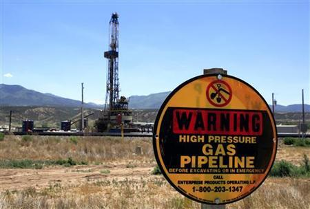 A drilling rig operates as a sign warns of underground natural gas pipelines outside Rifle, Colorado, June 6, 2012. REUTERS/George Frey