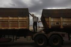 Um motorista de caminhão cobre seu rosto para proteger-se da poeira enquanto descarrega seu carregamento de grãos num terminal em Alto de Araguaia, Mato Grosso. 24/09/2012 REUTERS/Nacho Doce
