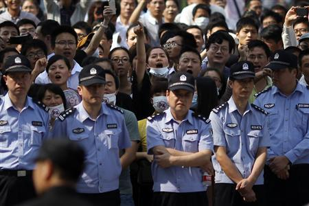 Protesters shout slogans behind a line of police officers during a protest against plans to expand a petrochemical plant in Ningbo, Zhejiang province in this October 27, 2012 file photo. REUTERS/Carlos Barria/Files