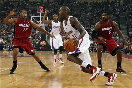 Jamal Crawford (C) of Los Angeles Clippers drives the ball between LeBron James and Garrett Temple of Miami Heat during the NBA China Games at Wukesong arena in Beijing October 11, 2012. REUTERS/David Gray