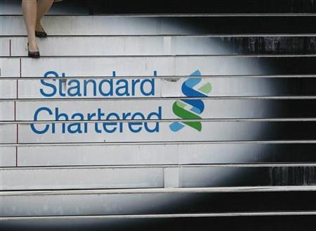 A woman walks down the stairs of the Standard Chartered headquarters in Hong Kong in this October 13, 2010 file photo. Picture taken October 13, 2010. REUTERS/Bobby Yip/Files