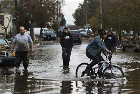 A man rides a bike past three others walking through water still sitting in the streets to survey damage from Hurricane Sandy in the New Dorp Beach neighborhood of the Staten Island borough of New York, November 1, 2012. REUTERS/Lucas Jackson