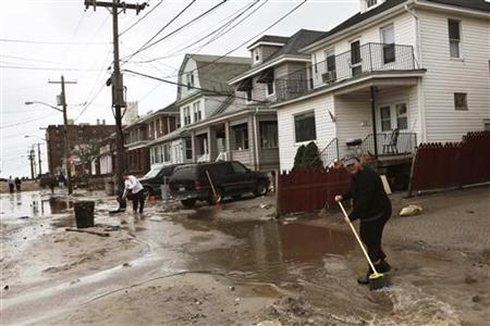 Citizens clean damaged and flooded streets in the borough of Queens in New York October 30, 2012 in the aftermath of the storm Sandy. REUTERS/ Gil Cohen Magen