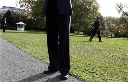 Secret Service agents watch as U.S. President Barack Obama (R) walks to Marine One as he departs for a trip to New Hampshire, from the South Lawn of the White House in Washington October 27, 2012. REUTERS/Joshua Roberts