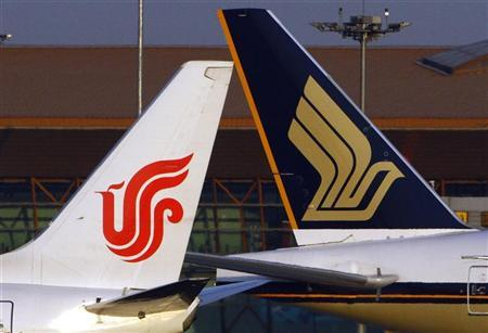 An Air China plane passes a Singapore Airlines plane on the runway at Beijing airport in this picture taken December 20, 2009. REUTERS/David Gray