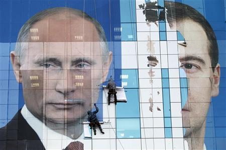 Workers attach a pre-election poster featuring then Russia's President Dmitry Medvedev (R) and Prime Minister Vladimir Putin, appealing to people to vote for the United Russia political party, onto an office building in the southern city of Krasnodar November 24, 2011. REUTERS/Eduard Korniyenko/Files