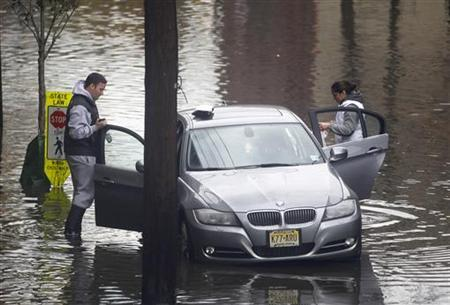 People check their car that had been covered with floodwaters on a street in Hoboken, New Jersey, October 31, 2012. REUTERS/Gary Hershorn