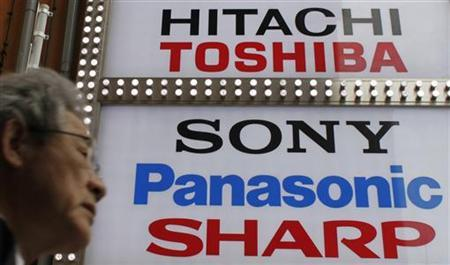 A man walks past logos of Japan's technology firms Hitachi Ltd, Toshiba Corp, Sony Corp, Panasonic Corp and Sharp Corp at the Akihabara electronics store district in Tokyo April 17, 2012. REUTERS/Toru Hanai