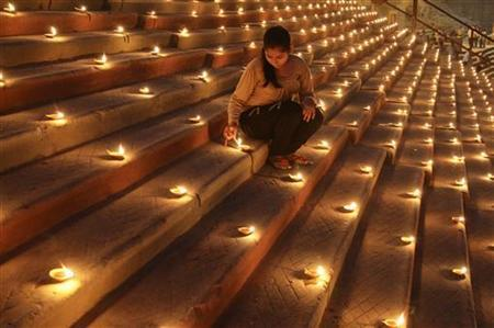 A Hindu devotee lights an earthen lamp on the steps of Sindhiya Ghat during the Karthik Purnima and Dev Diwali festival in Varanasi, November 10, 2011. REUTERS/Jitendra Prakash/Files