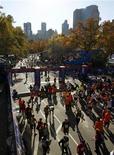 ¿Un símbolo de resistencia, o falta de tacto e inoportuna? La decisión del alcalde de Nueva York, Michael Bloomberg, de seguir adelante con la mayor maratón del mundo el domingo está creando una gran controversia en la metrópoli devastada por la tormenta Sandy. En la imagen de archivo, los participantes en el maratón de Nueva York del año 2011 atraviesan la linea de meta. REUTERS/Mike Segar