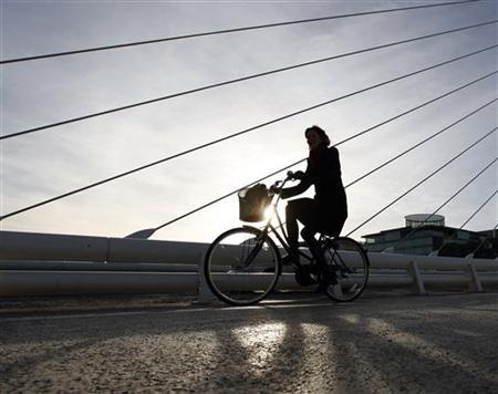 A woman cycles through the financial district of Dublin, February 24, 2011. REUTERS/Darren Staples