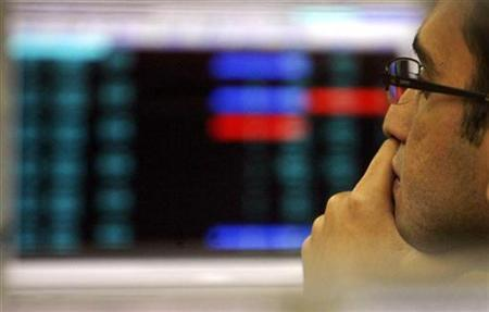 A stock broker looks at a terminal while trading at a stock brokerage firm in Mumbai November 17, 2008. REUTERS/Arko Datta/Files