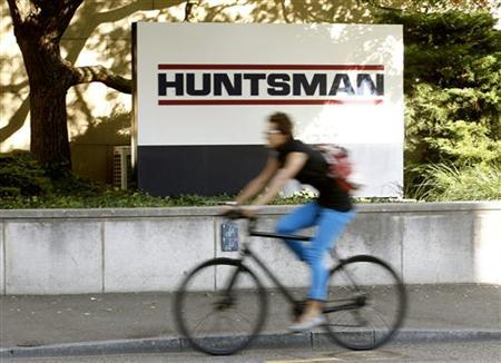 A woman cycles past the logo of U.S. chemical company Huntsman in front of a plant in Basel September 30, 2011. REUTERS/Arnd Wiegmann