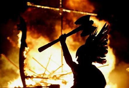 A Junior Up Helly Aa Viking lifts his axe upwards as a longboat burns behind him during the Up Helly Aa festival in Lerwick, the Shetland Islands, northern Scotland January 30, 2007. REUTERS/David Moir