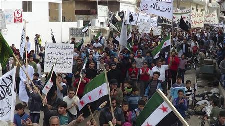 Demonstrators hold opposition flags during a protest against Syria's President Bashar al-Assad, after Friday prayers in Binsh near Idlib November 2, 2012. Banner reads ''The Syrian people are one''. REUTERS/Muhammad Najdet Qadour/Shaam News Network/Handout
