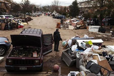 A man stands next to a damaged vehicle as he surveys flood damaged personal property thrown into the streets in the New Dorp Beach neighborhood of the Staten Island borough of New York, November 1, 2012. Deaths in the United States and Canada from Sandy, the massive storm that hit the U.S. East Coast this week, rose to at least 95 on Thursday after the number of victims reported by authorities in New York City jumped and deaths in New Jersey and elsewhere also rose. REUTERS/Lucas Jackson (UNITED STATES - Tags: ENVIRONMENT DISASTER)