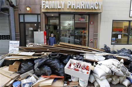A woman leaves a pharmacy damaged by floodwaters as debris is pilled in the streets in Hoboken, New Jersey, November 2, 2012. REUTERS/Gary Hershorn