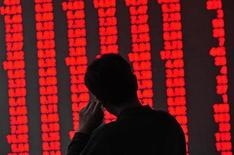 An investor looks at an electronic board showing stock information at a brokerage house in Shenyang, Liaoning province November 1, 2012. Mainland China shares started November on a strong note on Thursday, posting their best performance in more than three weeks, boosted by positive economic data and measures by some city governments to ease restrictions on the property sector. The figures on screen which are red in colour indicate rising prices. REUTERS/Stringer (CHINA - Tags: BUSINESS)