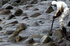 Conforme el petróleo se hace más escaso y caro, la industria podría inclinarse por fin en favor de una de las áreas más olvidadas de su negocio: la tecnología para limpiar vertidos de crudo. En esta imagen de archivo, un voluntario intenta limpiar una playa de petróleo en cabo Tourinán, en Galicia, el 20 de diciembre de 2002. REUTERS/Miguel Vidal/Files