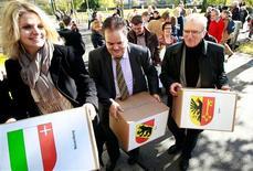 Los ecologistas suizos presentaron el viernes al Gobierno 120.000 firmas para forzar un referéndum sobre la limitación de la inmigración, canalizado el malestar por los niveles de población en su país. En la imagen, miembros del comité de ECOPOP cargan cajas con banderas de los cantones con las más de 120.000 firmas para su iniciativa de referéndum, el 2 de noviembre de 2012. REUTERS/Ruben Sprich