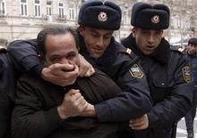 Полицейские задерживают демонстранта в Баку 12 марта 2011 года March 12, 2011. Азербайджан ужесточил наказания за уличные акции, как это сделало другое богатое нефтью постсоветское государство - Россия, чье несменяемое руководство тоже столкнулось с ростом протестных выступлений. REUTERS/Orhan Orhanov