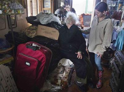 Brianna King (R) consoles her neighbor Barbara Cohen inside her hurricane damaged home in Long Beach, New York November 2, 2012. Four days after superstorm Sandy smashed into the U.S. Northeast, rescuers on Friday were still discovering the extent of the death and devastation in New York and the New Jersey shore, and anger mounted over gasoline shortages, power outages and waits for relief supplies. REUTERS/Shannon Stapleton